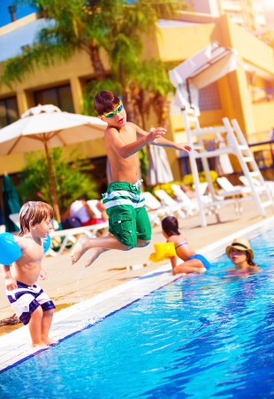 diving pool: Happy family having fun in the pool, son jumping into the water, relaxed in aquapark, beach resort, summer vacation, travel and tourism concept Stock Photo