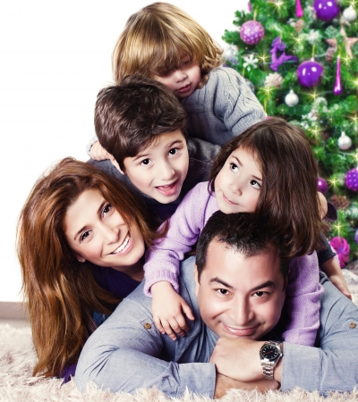 large family portrait: Closeup portrait of cute cheerful family lying down near Christmas tree at home, happy parents with three kids celebrate New Year holiday, love concept Stock Photo