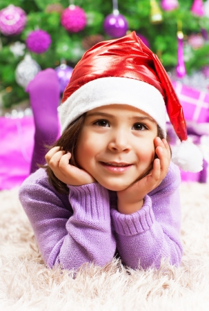 Closeup portrait of cute little arabic girl wearing red Santa Claus hat, lying down on the floor near beautiful decorated Christmas tree, New Year party  photo
