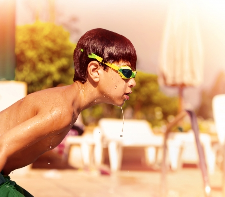 Side view of little active boy jump into the pool, wearing swimming goggles, water sport, summer holidays, happy and healthy lifestyle photo