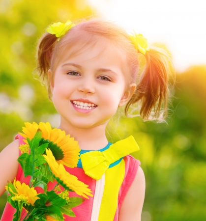 Closeup portrait of cute little girl holding bouquet of fresh yellow sunflowers outdoors, summer holiday, relaxation on backyard photo