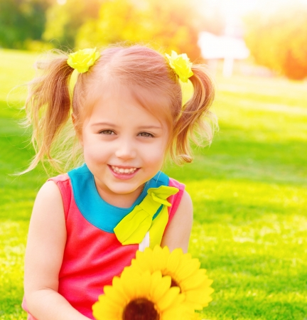 Adorable sweet child with sunflowers bouquet having fun in the garden, little girl enjoying summer nature, happiness concept photo
