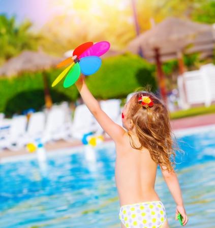 Pequeño bebé que se divierten en parque acuático, un juego de niños dulce con la flor del juguete colorido, disfrutando de las vacaciones de verano, descansando cerca de la piscina