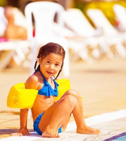poolside: Cute little girl sitting near pool, active happy childhood, summer holidays, having fun outdoors, wearing swimwear, joy and pleasure concept