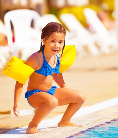 Cute little girl preparing to jump into water, having fun in the pool, luxury beach resort, summer time in daycare, holiday and vacation concept