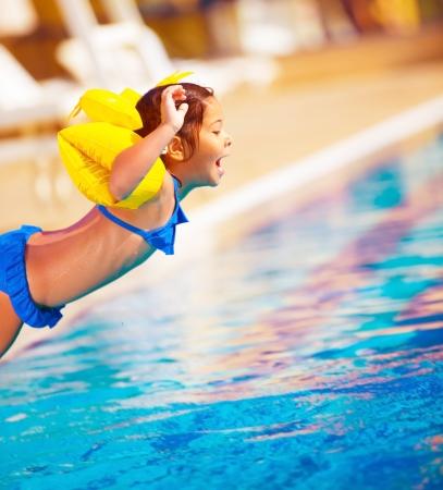 アクティブなライフ スタイル、陽気な甘い子水遊園地プールサイド、夏休み、旅の概念で水泳プールに飛び込むの少女