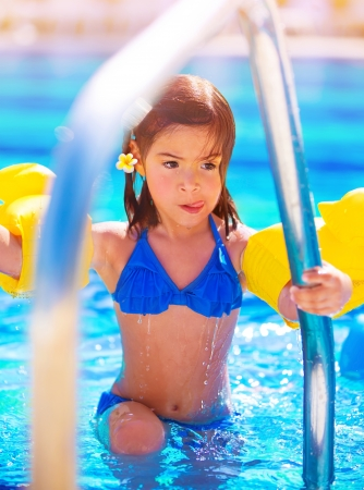 Little girl move out of the pool, having fun in water, summer vacation, beach resort, enjoying time in daycare, active childhood concept photo