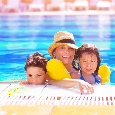 Closeup portrait of young arabic mother with two adorable children swimming in the pool, happy family on beach resort, happy summer holidays photo