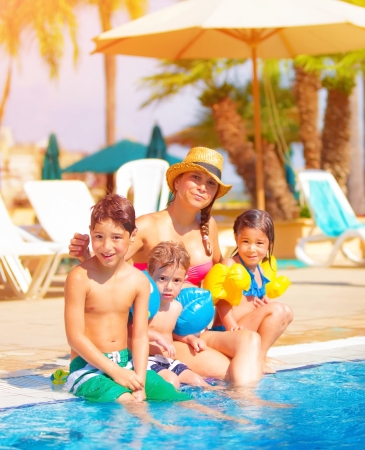 relax: Big family relaxed near poolside, happy young mother with three sweet child have fun outdoors on tropical resort, summer vacation, togetherness and love concept