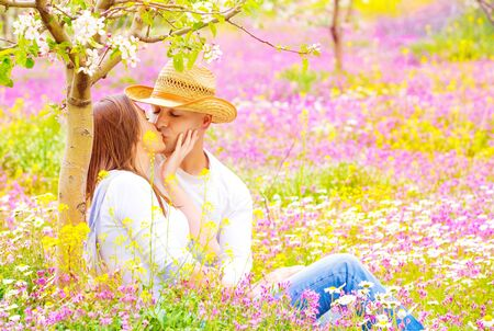Happy couple kissing outdoors, young family having fun on floral field, spending time together in summer garden, love concept photo
