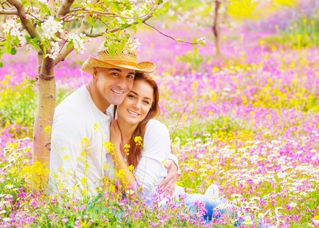 Portrait of attractive woman and handsome man sitting down on floral field, young lovers, having fun in the garden, romantic date, love concept photo