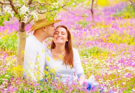 enamorados besandose: Los amantes felices besos al aire libre, cita romántica en jardín floreciente, hermosa joven familia, el afecto y el amor concepto