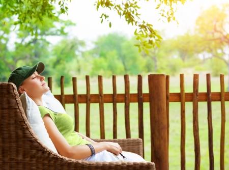 Cute girl resting on veranda, young traveler woman sleeping on backyard in sanatorium, relaxation outdoors, luxury resort, pleasure concept
