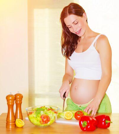 embarazada feliz: Mujer embarazada hermosa que cocina la ensalada en la cocina de su casa, la alimentaci�n saludable, cortar verduras, el concepto de embarazo feliz y saludable