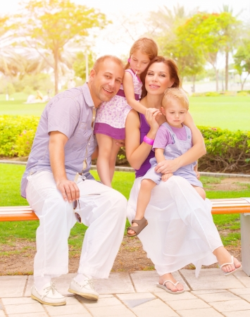 family baby: Cute family sitting on bench in the park, active lifestyle, little brother and sister with parent outdoors, parenthood concept