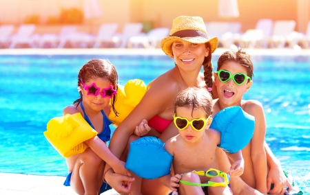 pool fun: Happy big family having fun at the pool, spending summer vacation together, wearing funny colorful sunglasses, enjoyment and pleasure concept Stock Photo