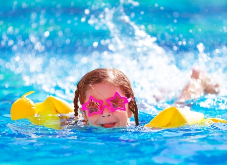 Closeup portrait of cute little arabic girl swimming in the pool, happy child having fun in water, beach resort, summer vacation and holidays concept Standard-Bild