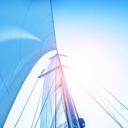 Close-up foto van zeil op de blauwe hemel achtergrond, felle zon licht, detail van het vervoer over water, zeilen sport, zeilboot op zee, zomer vakantie concept