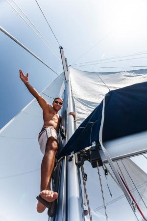skipper: Young cheerful skipper on the yacht, strong handsome sailor on vessel, luxury lifestyle, traveling and tourism, summer vacation