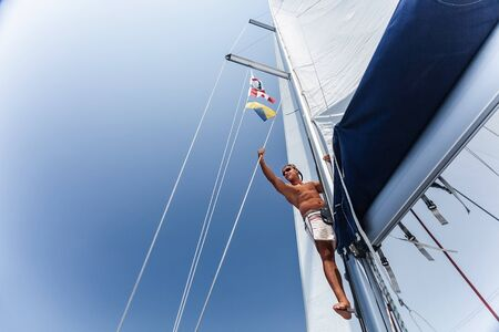 skipper: Handsome man working on sailing ship, cute sailor fixed sail, young cheerful skipper on the yacht, active lifestyle, summer vacation and traveling concept