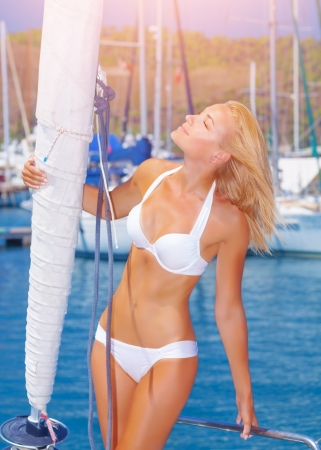 Sexy blond woman tanning on the sailboat, attractive girl enjoying bright sun shine in yacht port, summer vacation concept photo