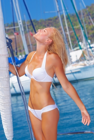Attractive girl wearing white sexy swimwear with closed eyes enjoying warm sunny day on the yacht deck, luxury lifestyle, holidays and vacation concept photo
