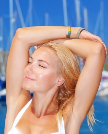 Closeup portrait of beautiful young lady with closed eyes on the beach, posing on yacht harbor background, warm sunny day, journey and trip concept photo