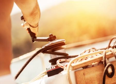 ヨット、身体の部分、明るい黄色の日没、ヨットの詳細、アクティブなライフ スタイル、ヨット スポーツ男持株クランクでクローズ アップ夏のリ