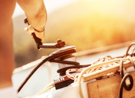 hand crank: Closeup on man holding crank on the yacht, body part, bright yellow sunset, sailboat detail, active lifestyle, yachting sport, summer relaxation concept