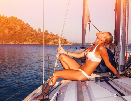 hot bikini: Sexy woman tanning on yacht, enjoying warm sunlight, seductive model wearing white stylish swimwear and posing on deck of sailboat in sunset light, summer holidays