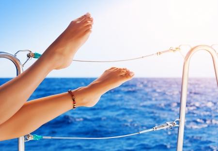 Primer en pies hermosos de las mujeres atractivas en el yate, vacaciones sin preocupaciones, el viaje en velero, estilo de vida feliz y saludable, concepto de placer