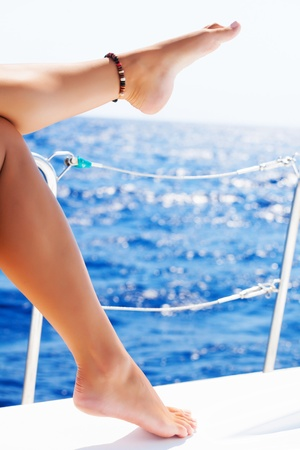Closeup on beautiful sexy womens feet on the yacht, body part, journey on sailboat, summer vacation, conceptual image of pleasure and enjoyment Stock Photo