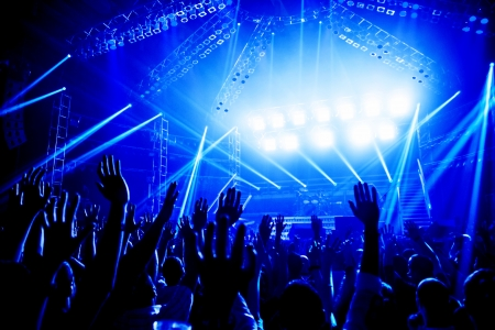 nightclub crowd: Rock concert, crowd of young people enjoying night performance, raised up and clapping hands, dance club, bright blue lights, music entertainment