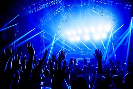 aplaudiendo: Un concierto de rock, multitud de jóvenes disfrutando de funcionamiento de la noche, levantó las manos y aplaudiendo, club de baile, luces azules brillantes, música de entretenimiento