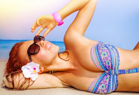 Closeup portrait of cute girl lying down on the beach, wearing sunglasses and blue swimsuit, enjoying dayspa, luxury spa resort, summer traveling concept photo