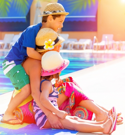 Happy family sitting near poolside, mother with two cute kids enjoying summer holidays, little sister and brother with young mom on luxury resort, love concept Stock Photo - 21386023