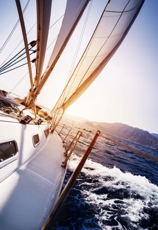 in action: Yate de lujo en la acción en el mar en el atardecer de fondo, vela deporte, transporte de agua, crucero de verano, los viajes y el concepto de turismo