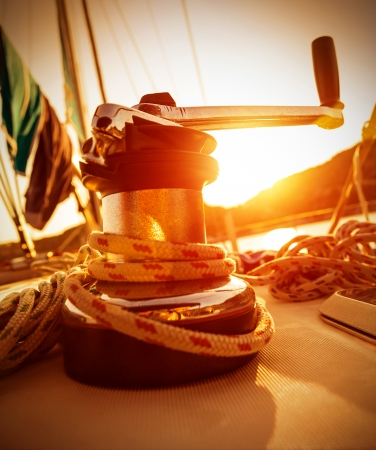 crank: Closeup on crank handle of yacht in warm yellow sunset light, sailboat detail, active lifestyle, water sport, luxury transport, summer tourism concept