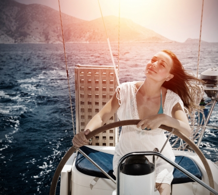 Woman behind the wheel yacht, enjoying sea nature and mountais landscape, active sailor girl, female driving luxury water transport, summertime concept photo