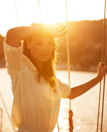 Portrait of beautiful woman on yacht deck in warm yellow sunset light, attractive model posing on sailboat, luxury cruise on the sea, summer vacation concept photo
