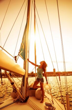 sailor girl: Beautiful sailor girl, pretty woman on the standing on yacht deck, warm sunset light, sailing sport, recreation on the sea, romantic summer holidays