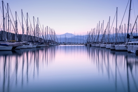 Large yacht harbor in purple sunset light, luxury summer cruise, sailboats in sunrise, leisure time, active life, vacation and holidays concept  Banque d'images