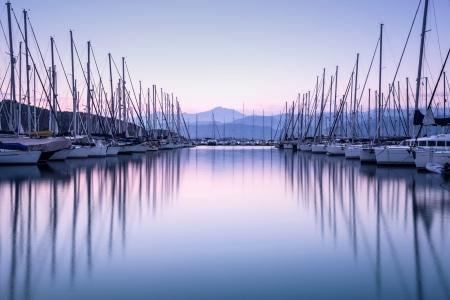Grote jachthaven in paarse zonsondergang licht, luxe zomer cruise, zeilboten in zonsopgang, vrije tijd, actieve leven, vakantie en feestdagen begrip
