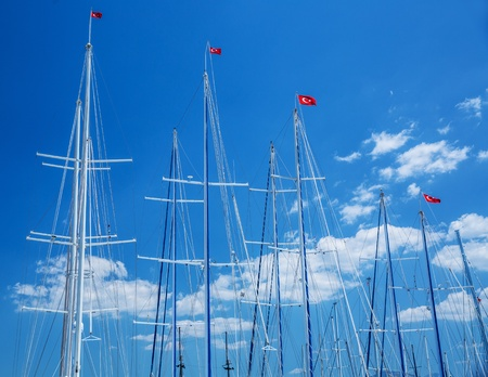 Yachts mast with turkish flags on blue sky background, sailing cruise to the Turkey, luxury summer vacation, relaxation in the sea, joy concept  photo