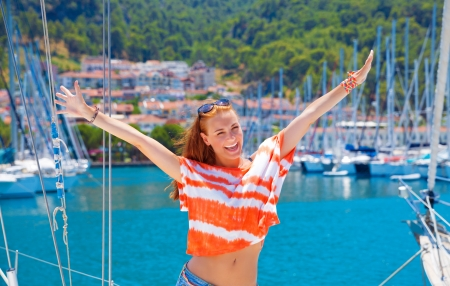 Beautiful happy woman having fun in yacht port, cute girl enjoying luxury sailing cruise, relaxation on the beach, active lifestyle, summer adventure concept photo