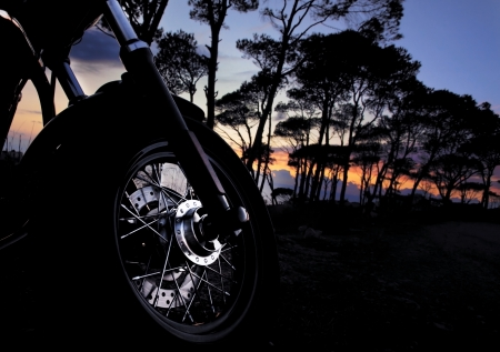 roadster: Closeup picture of motorbike detail on dark night forest background, motorcycle wheel on sunset, extreme transportation, adventure concept