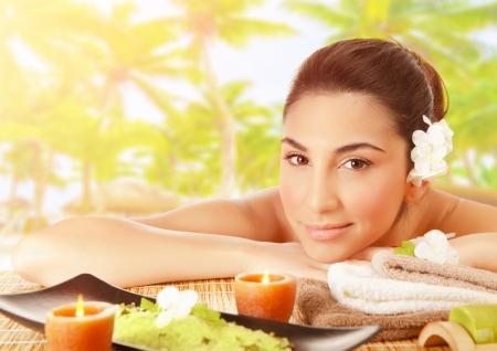 Close-up portret van leuke donkerbruine meisje liggend op de massagetafel buitenshuis, tropisch strand, toevlucht luxe spa, alternatieve therapie, zomer ontspanning concept
