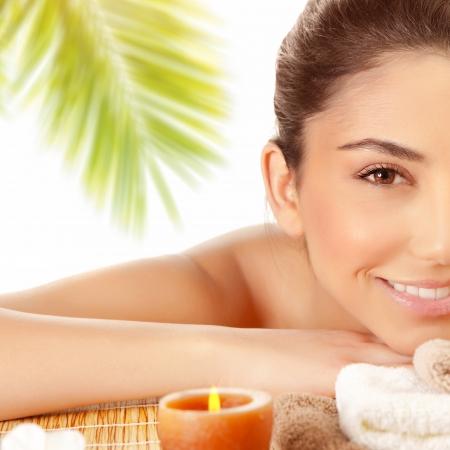 massaggio: Met� volto di sexy ragazza bruna godendo spa giorno sulla tabella di massaggio all'aperto, resort spiaggia esotica, palme, il benessere e il concetto di piacere Archivio Fotografico