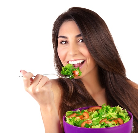 Closeup portrait of beautiful brunette woman eating salad isolated on white background, organic food, healthy lifestyle, dieting concept photo
