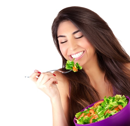 Closeup portrait of cute girl eating salad isolated on white background, enjoying fresh tasty vegetables with closed eyes, healthy lifestyle concept photo